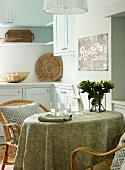 Kitchen table with tablecloth and wicker chairs in bright, country-house kitchen