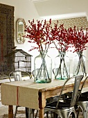 Branches of berries in glass vases on table and retro metal chairs in simple interior
