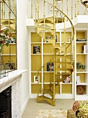 Vintage spiral staircase in front of modern fitted shelving against yellow wall in traditional setting