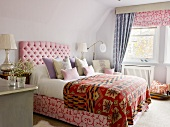 Double bed with upholstered headboard and ethnic bedspread in simple bedroom