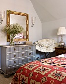 Bed with ethnic bedspread and pale grey vintage chest of drawers in attic bedroom