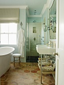 View through open door of washstand and free-standing vintage bathtub on honey-comb patterned floor tiles in front of window