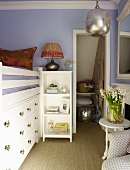 Lilac-painted child's bedroom with raised bed above built-in drawers next to open doorway with shelves in niche