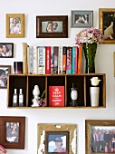 Small book shelf surrounded by framed photographs
