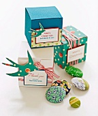 Various colourful buttons and cubic gift boxes with ribbons and labels