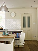 White, modern chair at rustic kitchen table in front of half-height shelving unit against tiled wall in rustic, traditional setting