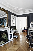 Diverse art works on a mantelpiece in front of a gold framed mirror in a drawing room with dark gray walls