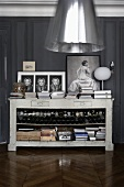 Antique kitchen counter with a cook book collection and wine bottles in front of a dark gray wall