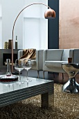 Wine decanter and glasses on low, metal coffee table in front of modern armchairs and copper-coloured arc lamp