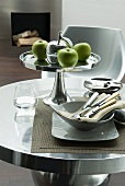 Green apples on silver fruit stand and bowl of cutlery on round table