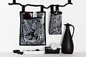Aufbewahrungstaschen mit schwarz-weißem Muster an Wand gehängt und schwarze Kanne auf weisser Ablage