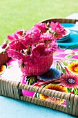 Pink flowers in bowl with pink knitted cover on floral tray