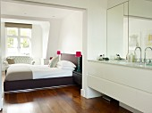 Modern washstand in ensuite bathroom and view of bed through open doorway
