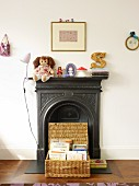 Basket with open lid in front of black fireplace with toys on mantelpiece