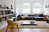 Low, wooden Bauhaus chair in front of floor-level, dark coffee table on flokati-style rug and grey designer sofa below window