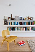 Low, wooden Bauhaus chair in front of white floating bookshelves