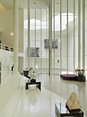 Zeitgenössische Skulpturen in einer Lobby mit Blick durch raumhohe Fenster auf den modern gestalteten Innenhof