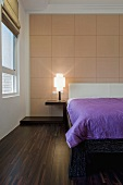 A screened wooden panel decorates a wall in a bedroom with a dark wooden floor