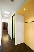 Dark wood flooring in a hallway with a curved, yellow wardrobe wall