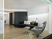 Designer sofa and armchair in a modern living room with suspended ceiling and indirect lighting