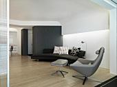 Designersofa und -Sessel in modernem Wohnzimmer mit abgehängter Decke und indirekter Beleuchtung