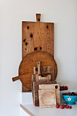 Collection of rustic chopping boards next to tomatoes and fruit bowl