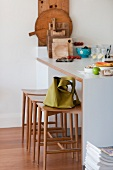 Green handbag on a narrow bar stool by a breakfast bar