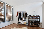 Clothes racks filled with stuff and shelves in a bedroom with large enclosed blind windows