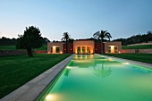 Swimming pool with Mediterranean style pool house at dusk
