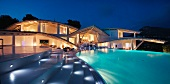 Modern home with illuminated steps and swimming pool at dusk pano