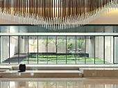 Deckenleuchte aus Vielzahl von Stäben im Foyer und Blick durch Fensterfront in gestylten Innenhof