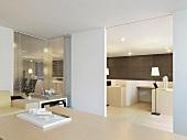 Architekturmodell auf Holztisch in modernem Besprechungsraum und Blick durch offene Schiebetür ins Büro