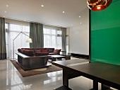 Esstisch vor grünem Glaspaneel und freistehende Eckcouch in modernem Wohnraum