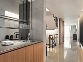 Open living with mini built-in kitchen and a view of a stairway