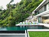 Holzdeck mit Liegestühlen am Pool eines in den Fels gebauten, zeitgenössischen Wohnhauses; Blick auf bewaldeten Hang