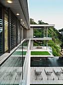 In Zonen unterteilte Aussenanlage eines Wohnhauses am Hang mit Liegestühlen auf Holzdeck und Rasenfläche am Infinity-Pool