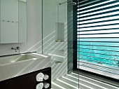 Sunlight streaming through blinds in modern bathroom