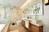 Vanity with a drawer cabinet under a large stone slab next to natural stone tiles in warm beige tones