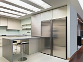 Large stainless steel refrigerator in a modern built-in kitchen with a breakfast bar and indirect ceiling lighting