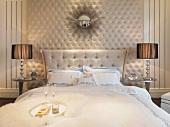 Stilisierter Sonnenspiegel über Doppelbett in klassisch elegant gestalteter Umgebung