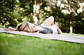 Woman laying on blanket in park