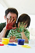 Father and son finger painting together