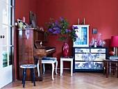 Glasvitrine auf kunstvoll bemalter Kommode, ein altes Klavier und verschiedene Vintage-Hocker vor rot getönter Wand