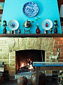 Brick open fireplace with antique silver jugs on mantelpiece and china plates with pictures of beetles on chimneybreast painted light blue