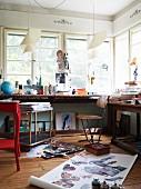 Maleratelier mit beladenen Tischen vor den Fenstern und Papierrolle mit naturgetreuen Schmetterlingsdarstellungen auf dem Fussboden