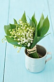 A bunch of lilly of the valley in a tin cup