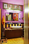 Cheerful bathroom in warm shades with collection of artworks and large painting reflecting in mirror