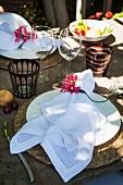 weiße Stoffserviette mit Blumendeko auf rustikal gedecktem Tisch