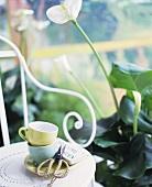 Tassenstapel auf weißem Metallstuhl neben Calla im Blumentopf auf Boden