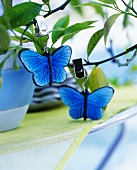 Decorative blue butterflies with clips hanging from a small tree